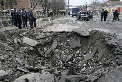 Investigators work the scene of Wednesday's suicide attack in the southern Russian region of Dagestan, where two suicide bombers killed 12 people.