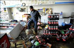 Hicham Ghamrawi of Cranston, R.I., surveys the damage to his convenience store Thursday. City officials gave free building permits to homeowners and businesses to jump-start recovery efforts.