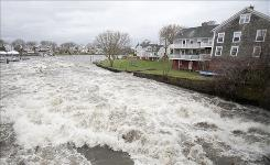 Floodwaters of Rhode Island's Pawtuxet River flow past homes on the Warwick side.