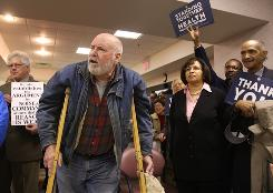 "Supporters of the new health care law who turned out Monday to hear Rep. Steve Driehaus in Cincinnati stand around a man on crutches who called Driehaus a ""phoney."" He would not give his name."