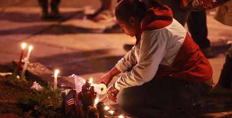 A woman participates in a candelight vigil for those slain in a drive-by shooting in Washington, D.C.