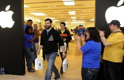 After being the first person in line, Jason Saucier is applauded as he leaves the Apple Store with his new Apple iPad at West Farms Mall in Farmington, Connecticut, on Saturday.