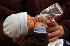 Diego Gomez drinks breast milk from a bottle during a newborn care class in Aurora, Colo., in February. During the last year of recession, the Metro Community Provider Network, which treats low-income patients, has seen more than a doubling of clientelle.
