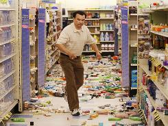 Rite Aid Pharmacy manager Robert Escalante walks past fallen beauty products in his store in downtown Calexico, Calif., Monday, after the area was struck by a powerful earthquake on Sunday.