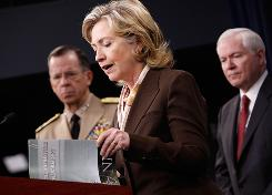 Secretary of State Hillary Rodham Clinton reads from a document on nuclear policy at a news briefing with Chairman of the Joint Chiefs of Staff Mike Mullen, left, and Defense Secretary Robert Gates.