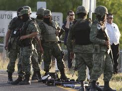 Mexican soldiers gather at the site of a firefight between gunmen and troops on the outskirts of Monterrey in northern Mexico last week.  Drug violence has claimed 18,000 lives since 2006.