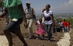 People displaced by the earthquake walk to a bus as they are relocated from the Petionville Golf Club to a new camp in Port-au-Prince on Saturday.