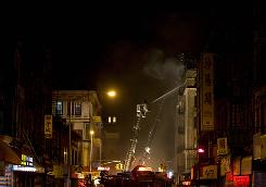 Firefighters battle a seven-alarm fire at 285 Grand St. in New York's Lower East Side neighborhood Monday.