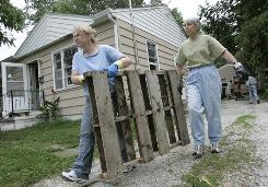 Volunteers Lynda Albaugh, left, and Linda Railey haul debris from a home in Des Moines in March.