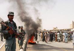 Afghan police stand guard as protesters burn tires during a demonstration on the outskirts of Kandahar city on Monday.