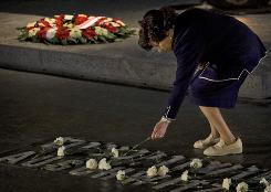 Relatives of Holocaust victims lay flowers next to the names of concentration camps, during a ceremony marking the annual Holocaust remembrance day in the Hall of Remembrance at the Yad Vashem Holocaust Memorial in Jerusalem on Monday.
