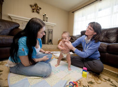 Nurse Cheryl Spicer, right, visits Nicole McCartney, new mother of 5-month-old Jazleen, at her home home in Carlisle, Pa.
