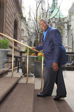 Baseball Hall of Famer Hank Aaron walks up steps outside of the Palace Hotel in New York City where he attended a conference on arthritis treatment on April 7. Aaron suffers from arthritis in both knees.