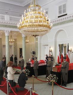 Mourners kneel down in front of the coffins of late Polish President Lech Kaczynski and his wife, Maria.