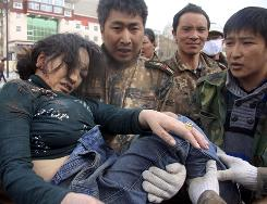 In this photo released by China's Xinhua News Agency, an injured woman is rescued Wednesday after a quake in Yushu County, northwest China's Qinghai Province.