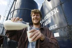 John Clark pours raw milk into a glass at Applecheek Farm in Hyde Park, Vt.,The debate over the health attributes and risks of raw milk are spilling into statehouses and courtrooms across the country as proponents of unpasteurized dairy products push to make it easier for people to buy them.