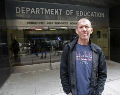 New York City public school teacher David Suker, who has been assigned to a rubber room for more than a year while he awaits the results of a disciplinary hearing, stands in front of New York City's Department of Education building.