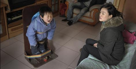 Six-year old Peng Jing, who has cerebral palsy, cries out with the pain of standing in the contraption his parents copied from a hospital device to correct his disabled legs and improve his walking ability. His parents estimate they have spent over $15,000 at hospitals, and tried many different drugs and physical therapy techniques.