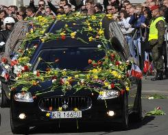 Flower-strewn hearses carry the coffins of late Polish President Lech Kaczynski and his wife, Maria, as they make their way to the St. Mary's Basilica Sunday in Krakow, Poland.