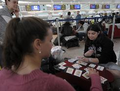 Fliers play cards as they wait at the El Prat Airport in Barcelona Sunday. Barcelona and 13 other airports in the country were closed until at least 8 p.m. due to the cloud of volcanic ash over Europe.