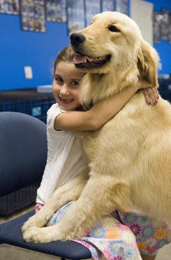 Rachel Walz hugs her dog Cappi at the Canine Assistants training facility in Atlanta in 2006.