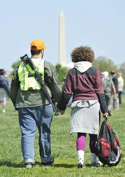 "Kevin and Mina Patrick of Morgantown, W.Va., walk with other gun rights advocates as a demonstration of their constitutional rights to bear arms during the ""Restore the Constitution"" rally at Gravelly Point Park in Arlington, Va., on Monday,"