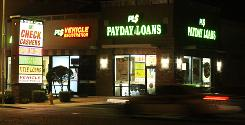 Neon signs illuminate a 24-hour payday loan business in Phoenix.