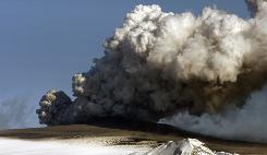 A plume of ash rises from the volcano in southern Iceland's Eyjafjallajokull glacier on Monday. Meteorologists in Iceland said eruptions from the volcano were weakening and the ash was no longer rising to a height where it would endanger large commercial aircraft.