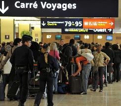 Passengers wait to check in at Paris-Orly Airport on Monday.
