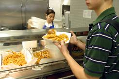 A student at Bowie High School in Austin, Texas, grabs french fries for lunch. About one-quarter of those age 17 to 24 are too heavy to serve, so military leaders are taking aim at foods served in U.S. schools.