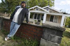 Derrick Evans, founder of Turkey Creek Community Initiatives, leans against the front wall of his great-grandfather's home in Gulfport, Miss. Evans says environmental efforts often ignore minority areas.
