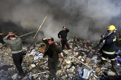In this 2007 photo, Iraqis grieve amid the rubble after a car bomb attack in Baghdad. Today, such violence in Afghanistan is contributing to rising numbers of deaths among U.S. contractors.