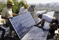 California Green Design employees, from left, Arin Gharibian, Hayk Mkrtchayan and Edward Boghosian, assemble solar electrical panels on the roof of a home in Glendale, Calif., March 23. Costs of photovoltaic technology are coming down.