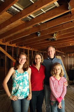 Wendy Koch and her husband, Alex, and children Mary, 13, left, and Grace, 9, stand in a home that will be torn down but the materials are going to be recycled.
