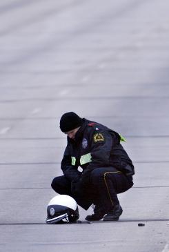 Dallas Police Senior Corporal David Frykholm inspects the helmet of an officer who died in a motorcycle crash while escorting U.S. Sen. Hillary Clinton's motorcade in Dallas in 2008.