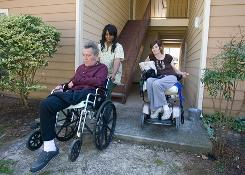 Sharima Jones, a certified nursing assistant, assists Richard Hasselbach outside the apartment he rents with Deborah Kadlec, right.