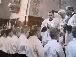 Plaintiff John Doe 16 is suing the Vatican and Pope Benedict XVI, claiming that they knew Rev. Lawrence Murphy, back left with hands in praying position, was a child molester. In this photo, Murphy watches as Holy Communion is administered to the boys at St. John's School for the Deaf in St. Francis, Wis.