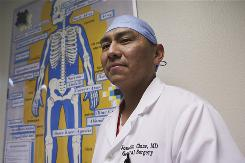 Chief of surgery Joachim Chino, 37, a Navajo-Acoma Native, stands next to a skeletal poster in English and Navajo at the Tuba City Regional Health Care Corp., in Tuba City, Ariz.