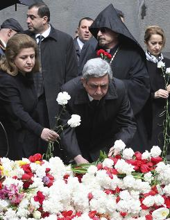 Armenian President Serge Sarkisian, center, and his wife Rita, left, lay flowers at a memorial to Armenians killed by the Ottoman Turks, as they mark the 95th anniversary of the mass killings, in Yerevan, Armenia, on Saturday.
