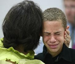 Donovan Weise cries on the shoulder of a sympathetic friend at the candlelight vigil for Adam Weise in Yorktown, Texas, on Friday night.