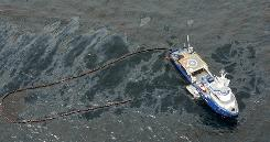 A boat enters a sheen of oil with a containment boom about 7 miles from where the drilling rig sank.