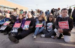 Protesters in Broadview, Ill, try to prevent vehicles from transporting immigrants to the airport for a deportation flight Tuesday. About 24 demonstrators were arrested.