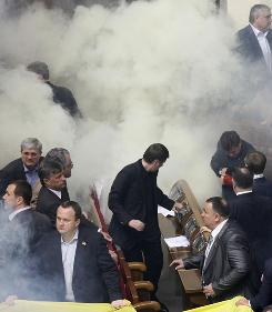 Smoke from smoke bombs fill the session hall during ratification Tuesday of the Black Sea Fleet deal with Russia, in parliament in Kiev, Ukraine,