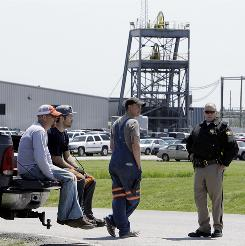 Miners and a Hopkins County Sheriff's deputy, right, stand near the entry portal to the Webster County Coal Dotiki Mine No. 4 in Nebo, Ky., on Thursday.