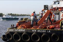 Workers load oil booms onto a crew boat in Venice, La., to assist in the oil cleanup in the Gulf of Mexico from the Deepwater Horizon oil rig explosion last week.