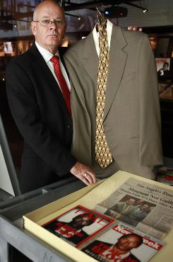 Mike Gilbert, former agent for O.J. Simpson, holds Simpson's suit at the Newseum in Washington D.C.