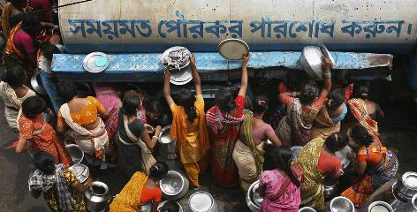 "Slum dwellers try to collect drinking water from a tanker in Dhaka, Bangladesh. Bangla reads,""Clear municipal tax in time."" A young democracy plagued by corruption and natural disasters where nearly half the population lives on less than $1 a day, the Muslim nation has vast experience beating back diarrhea tied to annual monsoon flooding, unclean drinking water and poor sanitation."