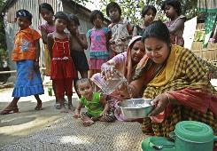 Children watch as Rahima Begum, 45,  helps Taslima Akter, 28, right, make lifesaving oral rehydration salts, or ORS,  for diarrhea patients at Borongo Khola village in Manikgonj, outskirts of Dhaka, Bangladesh.