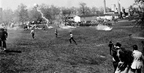 Ohio National Guardsmen throw tear gas at students across the campus lawn at Kent State University during an anti-Vietnam War demonstration at the university on May 7, 1970.  The Guard killed four students and wounded nine.