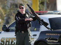 A Pinal County Sheriff's deputy prepares to search for a suspect that shot a fellow deputy with an AK-47 on Friday near Stanfield, Ariz.